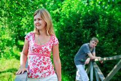 Couple on bridge. Girl standing in the foreground, boy looking at her on the blur backgroung Royalty Free Stock Photo