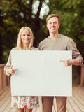 Couple on the bridge with blank white board Royalty Free Stock Photography