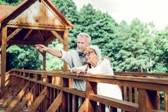Cheerful couple standing on the wooden beautiful brown bridge stock image