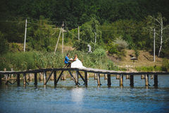 Couple on Bridge over River. Couple sitting on wooden bridge over river Royalty Free Stock Images