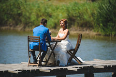 Couple on Bridge. Couple sitting at table on bridge in sunlight Stock Photo