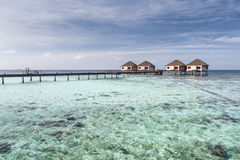 Couple on bridge to Water villas on crystal clear water at tropi Royalty Free Stock Photos