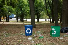 A couple of colorful recycling bins on a blurred natural background. Containers for garbage recycling. Ecology. A couple of bright blue and green recycling bins Royalty Free Stock Images