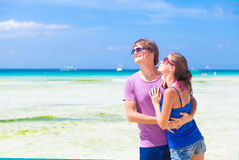 Couple in bright clothes hugging on tropical beach Stock Photos