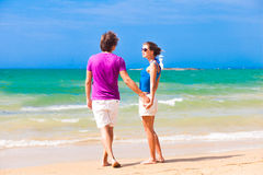 Couple in bright clothes on tropical beach holding Stock Images