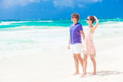 Couple in bright clothes on tropical beach holding Stock Image