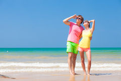 Couple in bright clothes on tropical beach looking. At sky. This image has attached release Royalty Free Stock Images