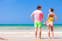 Couple in bright clothes on tropical beach in Stock Photography