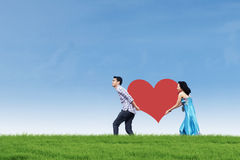 Couple bring heart card on green field Stock Photos
