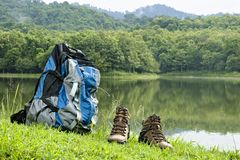 Couple Brown men`s hiking mid ankle shoes and backpack. Tropical forest and pool green background. Horizontal color image royalty free stock photos