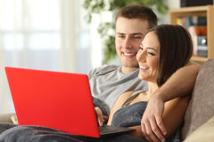 Couple browsing internet in a red laptop Stock Images