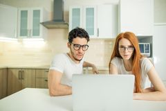 Couple browsing internet together sitting at table and smiling and read screen. Young couple browsing internet together sitting at table and smiling happily as Stock Photo