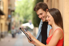Couple browsing a tablet in the street royalty free stock photo