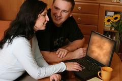 Couple Browsing WWW. Smiling couple sitting with laptop at home Stock Images