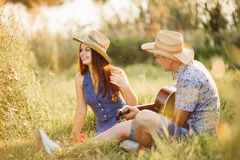 Couple of brunette girlfriend and boyfriend sitting on grass at meadow smiling and having fun together, wearing in hats. Man singi Royalty Free Stock Image