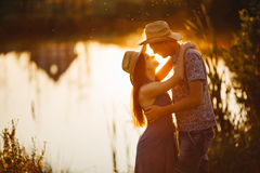 Couple of brunette woman and man in hat embracing, sensuality looking each other. Girlfriend and boyfriend standing on pier of riv Royalty Free Stock Image
