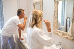 Couple brushing teeth in front of mirror Royalty Free Stock Photos