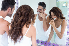 Couple brushing teeth while looking in mirror. Young couple brushing teeth while looking in mirror at bathroom stock image