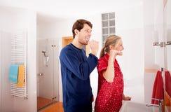 Couple brushing teeth Stock Images