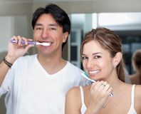 Couple brushing their teeth Stock Images