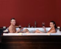Couple in bubble bath. Couple sitting in bubble bath, having red wine in wellness environment, looking at camera stock image
