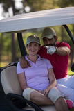 Couple in buggy on golf course Royalty Free Stock Images