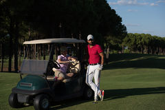 Couple in buggy on golf course Stock Photo