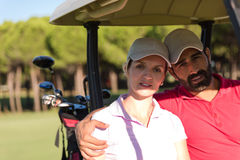 Couple in buggy on golf course Stock Photography