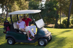 Couple in buggy on golf course Stock Images