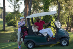 Couple in buggy on golf course Royalty Free Stock Photos