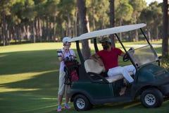 Couple in buggy on golf course Stock Photos