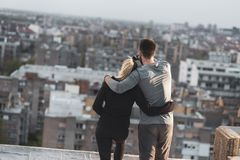 Couple on a building rooftop terrace. Young couple standing on a building rooftop terrace, hugging and enjoying the view over the city royalty free stock image
