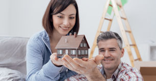 Couple building their house. Happy smiling couple holding a model house, they are building their home together, real estate and construction concept Royalty Free Stock Photography
