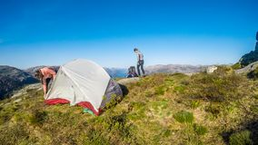A couple building up a tent in the wilderness in Norway. stock photography