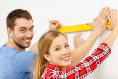 Couple building using spirit level to measure Royalty Free Stock Photos
