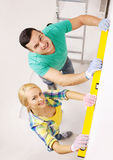 Couple building using spirit level to measure Stock Images