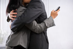 Couple business hugging but still using phone Royalty Free Stock Image