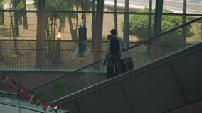 Couple of business partners moving on escalator in airport, arriving for meeting. Stock footage stock footage
