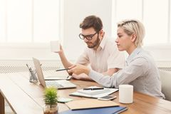 Couple of business partners work at modern office. Couple of serious business partners working in modern office. Two coworkers discussing new project while Royalty Free Stock Photo