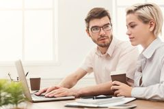 Couple of business partners work at modern office. Couple of serious business partners working in modern office. Two coworkers discussing new project while Stock Image
