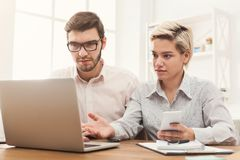 Couple of business partners work at modern office. Couple of worried business partners working in modern office. Two coworkers having trouble while working on Royalty Free Stock Photos