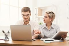Couple of business partners work at modern office. Couple of worried business partners working in modern office. Two coworkers having trouble while working on Stock Photography