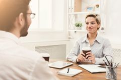Couple of business partners work at modern office. Couple of young business partners working in modern office. Smiling women discussing new project with her Royalty Free Stock Photos