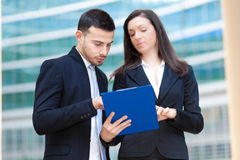 Couple of Business People outdoor. Group of Business People reading some documents royalty free stock image