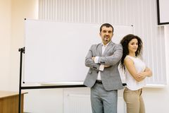 Businessman and businesswoman on the presentation background. Business confidence concept. Copy space. Stock Images