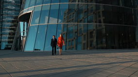 Couple of business people walking near Business centre. Slow motion. Two successful young businesspeople walk with glass modern building at bg. Businessman and stock video footage