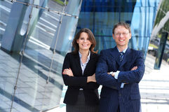 A couple of business persons in formal clothes. A couple of smart Caucasian business persons standing in formal clothes. The image is taken on a modern Royalty Free Stock Image