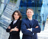 A couple of business persons in formal clothes. A couple of smart business persons standing in formal clothes. The image is taken on a modern architectural Stock Photos