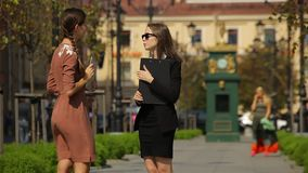 Couple of business women taking conversation on the street of the city. Two female office worker with tablet and map-case. They shaking hands and saying stock footage