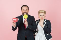 Couple of businessmen loving candy and presents. valentine concept shooting in studio. Man in black suit with lollipop royalty free stock photos